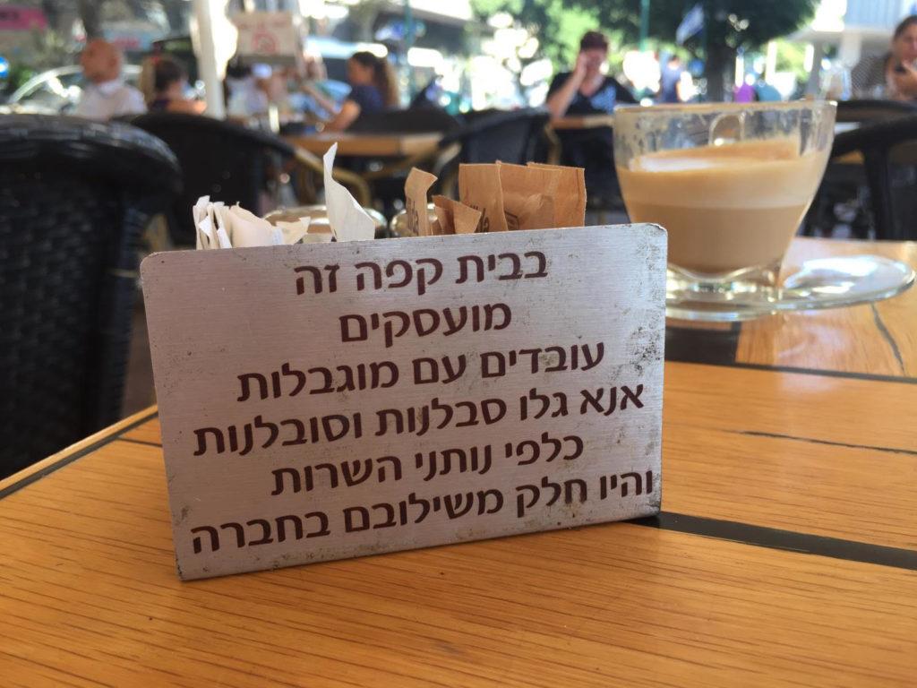 Ein kleines Schild auf den Tischen weist darauf hin: hier arbeiten besondere Menschen. Mit Depressionen, Autismus, Verhaltensstörungen. Café Emanuel